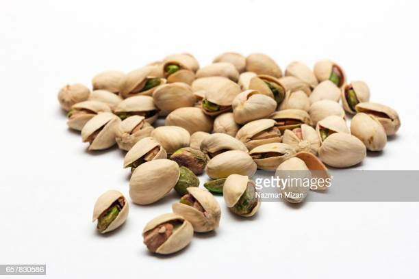 A close up shot of pistachios on white background.