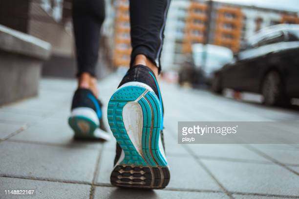 close up shot of runner's shoes - city life stock pictures, royalty-free photos & images