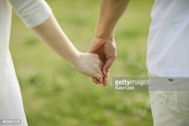 Close up shot of senior couple holding hands