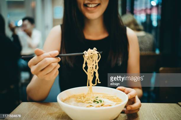 close up shot of smiling young asian woman eating japanese soup noodles in restaurant - ramen noodles stock pictures, royalty-free photos & images