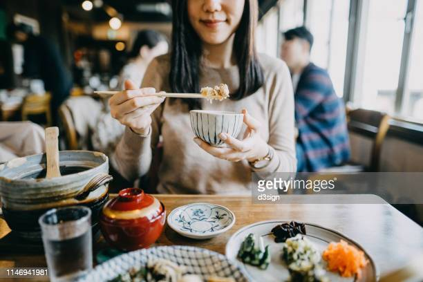 close up shot of smiling young woman enjoying japanese cuisine with various side dishes, miso soup and green tea in restaurant - japanese food stock pictures, royalty-free photos & images
