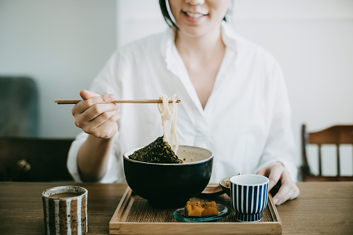 Close up shot of smiling young woman enjoying Japanese udon soup noodles with side dishes and green tea in restaurant - gettyimageskorea