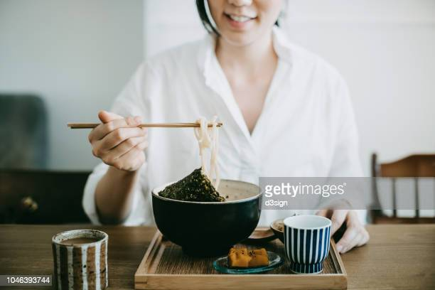 Close up shot of smiling young woman enjoying Japanese udon soup noodles with side dishes and green tea in restaurant