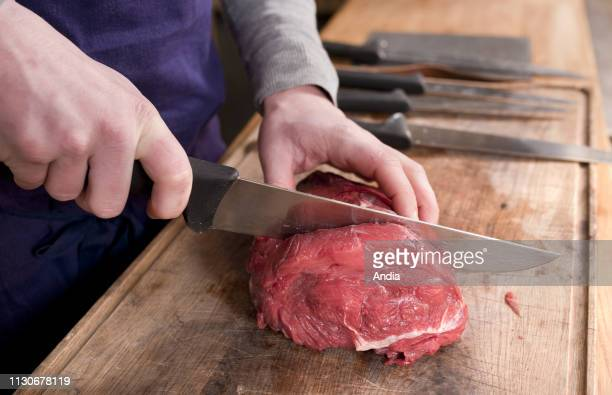 Close up shot of the hands of a butcher cutting a piece of meat