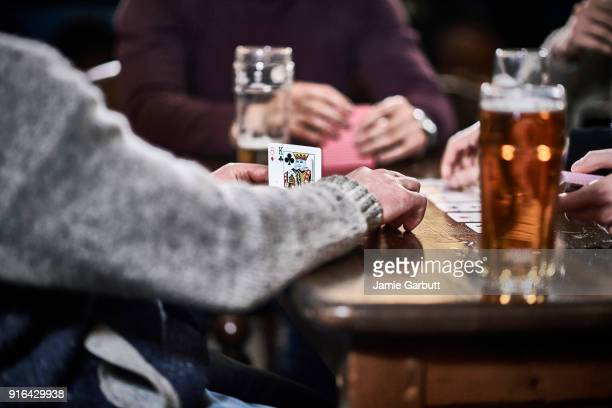 close up shot of the hands of a group of men playing cards - poker stock-fotos und bilder