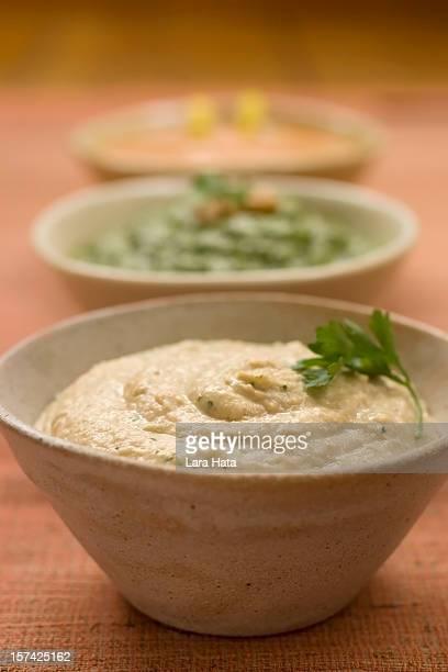 Close up shot of three bowls of hummus on wood table