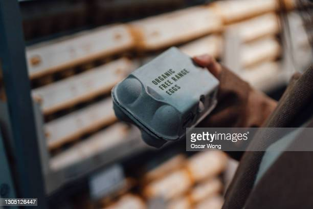 close up shot of woman holding a box of organic free-range eggs - merchandise stock pictures, royalty-free photos & images