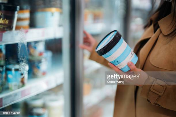 close up shot of woman holding a cup of vanilla flavour ice cream in supermarket. - china: through the looking glass bildbanksfoton och bilder