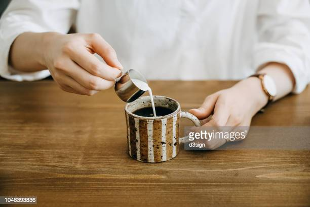 close up shot of woman pouring milk in coffee cup and ready to enjoy it - milk pour stock photos and pictures