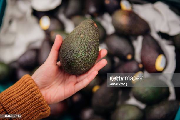 close up shot of woman's hand holding avocado in grocery store - avocado stock pictures, royalty-free photos & images