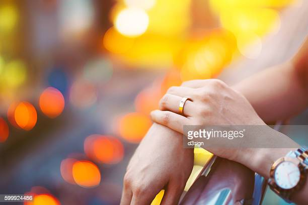 close up shot of woman's hand with a golden wedding ring against illuminated city street light. - gold rush imagens e fotografias de stock