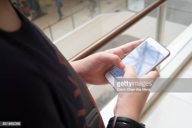 close up shot of young chinese asian hands using mobile phone - mensajería instantánea fotografías e imágenes de stock