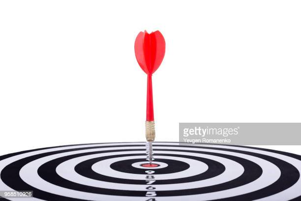 close up shot red dart arrow on center of dartboard, metaphor to target success, winner concept, isolated on white background with clipping path - aiming stock pictures, royalty-free photos & images
