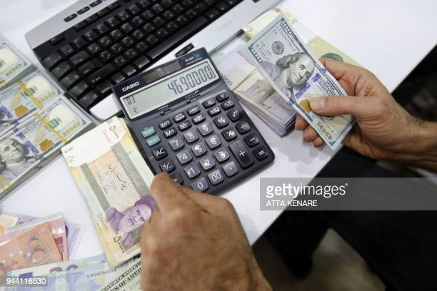 A close up shot shows an Iranian holding US dollar notes in his hand with Iranian riyals on the table bearing portraits of the late founder of the...