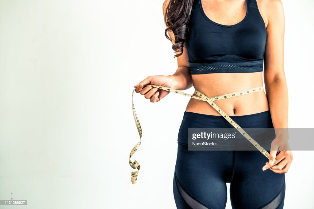 Close up shot woman with slim body measuring torso : Stock Photo