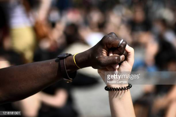 Close up shows a white person and a black person hold hands during a demonstration calling for justice for George Floyd, who died May 25 after being...