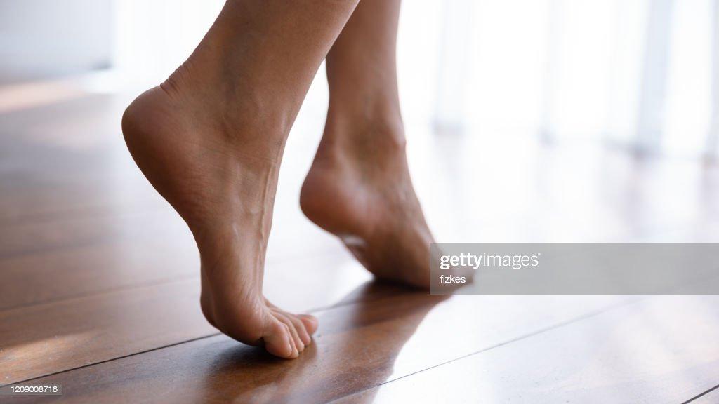 Sluit omhoog zijmening mooie vrouwelijke voeten op houten vloer : Stockfoto