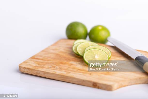 close up sliced of the green lime and seed with a knife place on wooden board in a kitchen on white - planche à découper photos et images de collection