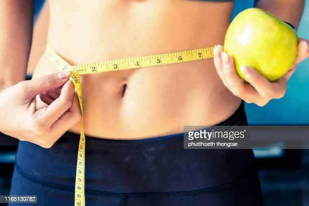close up slim young woman measuring her waist with a tape measure.healthy lifestyle, diet nutrition concept. - celulitis fotografías e imágenes de stock