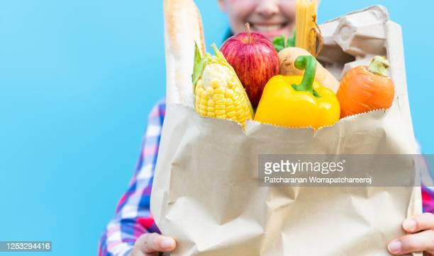 close up smiling asian woman carrying grocery shopping bag full of fresh vegetables and fruit. female holding paper bags full of groceries. - vegetais - fotografias e filmes do acervo