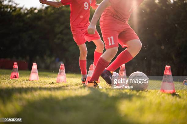 Close up soccer players practicing with a ball