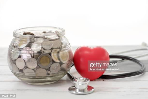 close up stack of coins and hand holding red heart background, saving money for healthcare and manage for success business concept