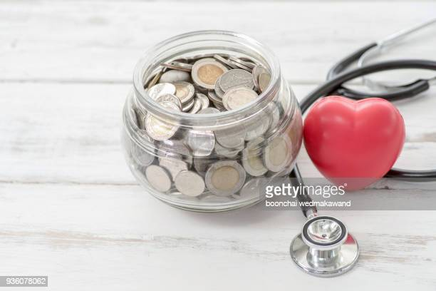 close up stack of coins and hand holding red heart