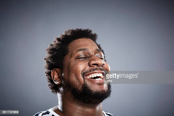 Close up studio portrait of mid adult man laughing