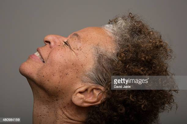 Close up studio portrait of senior woman with head back and eyes closed