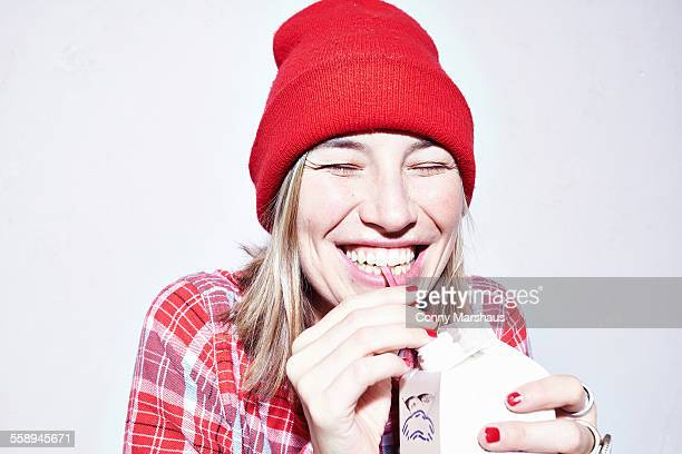 Close up studio portrait of young woman in red hat drinking juice