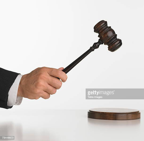 Close up studio shot of judge's hand with gavel