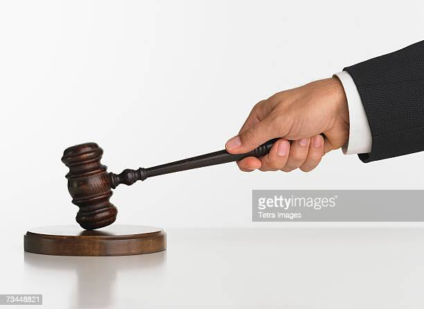 Close up studio shot of judge's hand with gavel