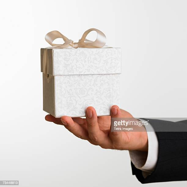 Close up studio shot of man holding gift