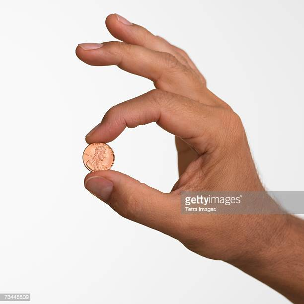 close up studio shot of man holding penny - us penny stock pictures, royalty-free photos & images