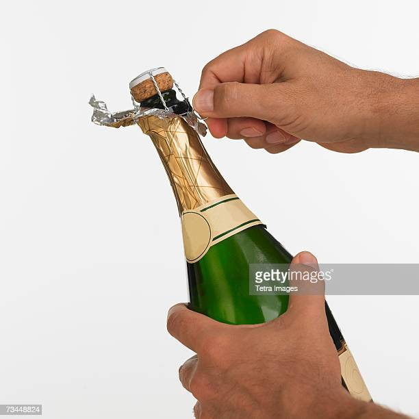 Close up studio shot of man opening champagne