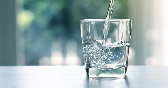 Close up the  pouring purified fresh drink water from the bottle on table in living room 803155598