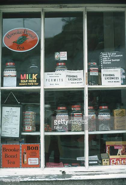 A close up the window of Prenteg Post Office Wales which is displaying fishing and TV licenses sweets and milk for sale September 1969