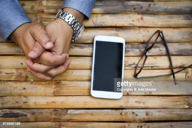 Close up top view business man's hand with smart phone and eye glass, black isolated screen over wooden background
