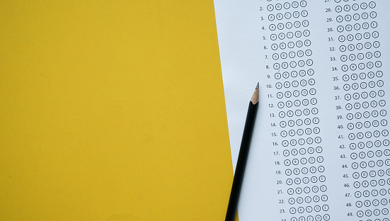 close up top view of black pencil over exam answer sheet paper with multiple choice on yellow background for world literacy day and education concept 1146008229