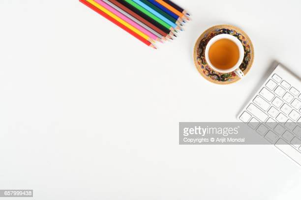 close up top view office table with colour pencils, green tea and computer keyboard - website template stock photos and pictures