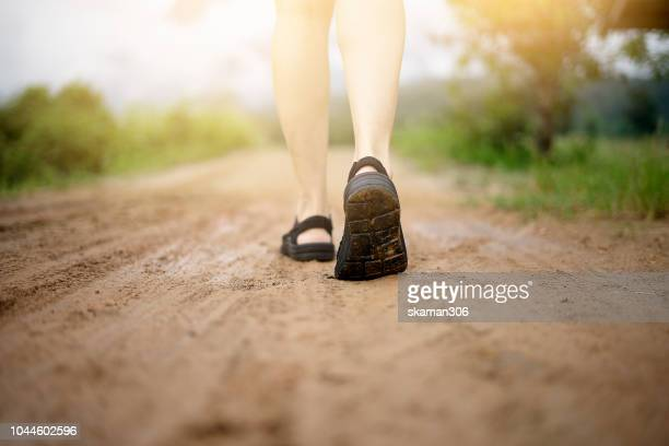 Close up traveller walking on dirt road