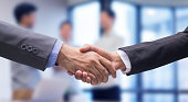 close up two businessman hand shake together for agreement successful on blur group of businesspeople talking in meeting room , achievement concept