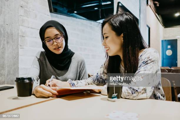 close up two women discuss about success - rifka hayati stock pictures, royalty-free photos & images