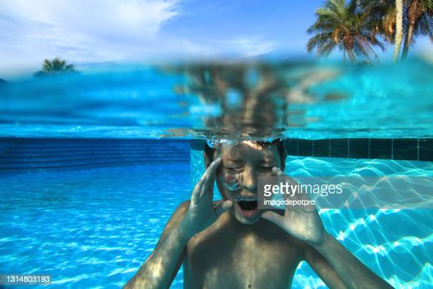 close up underwater portrait of teenage boy in swimming pool - partially sighted stock pictures, royalty-free photos & images