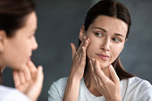 Close up unhappy woman looking at acne spots in mirror