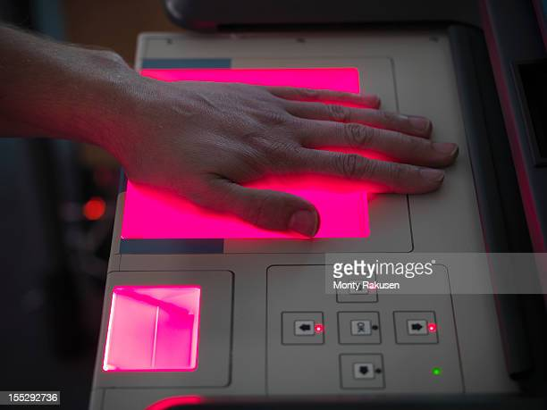 Close up up man scanning hand for fingerprints on machine in laboratory