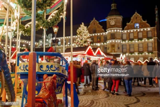 close up view at vibrance delicate carousel and blur background of night illuminated atmosphere of weihnachtsmarkt, christmas market at marktplatz around old town hall in düsseldorf, germany. - düsseldorf stockfoto's en -beelden