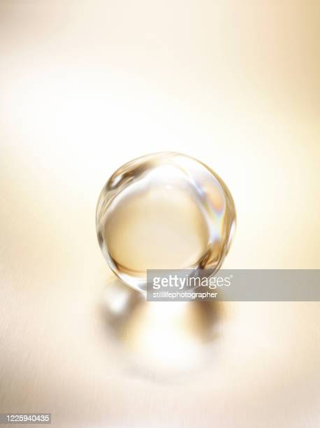 close up view in a 45 degree angle of a shining clear water droplet on a light gold metallic surface with reflection - goutte état liquide photos et images de collection