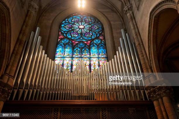 close up view of a church pipe organ and blue decorated glass window above - emreturanphoto stock pictures, royalty-free photos & images