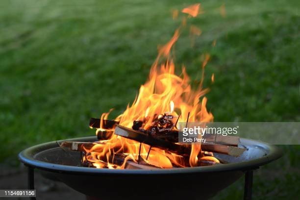 close up view of a fire pit (fire ring) burning wood on a patio - fire pit stock pictures, royalty-free photos & images